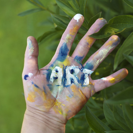 Painted word Art on a human hand, green foliage in the blurred background, concept of visual arts Stock Photo