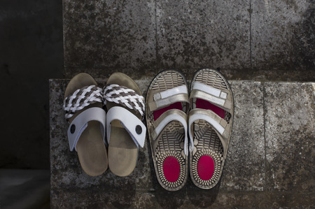 stair well: Two pairs of well used walking shoes on a stone stair concept of healthy lifestyle overhead shot Stock Photo