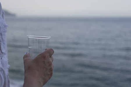 focus shot: Plastic glass of water in female hand sea in the blurred background selective focus shot