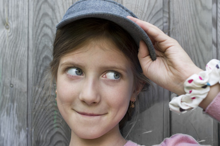 gaze: Portrait of a funny girl of 7 with a side gaze and pursed lips, wooden wall in the background
