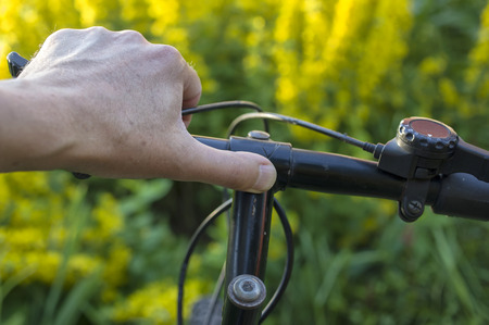 gripping: Male hand gripping a bicycle handlebar, closeup shot, yellow flowers in the blurred background