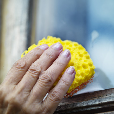 cleaning supplies: Female hand cleaning window by sponge and cleaning supplies, outdoor square shot with selective focus Stock Photo