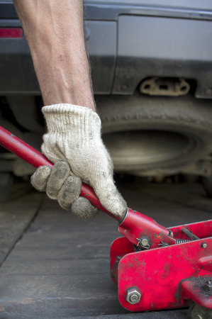 lifting jack: Male hand pushing a trolley jack under a car, vertical outdoor shot