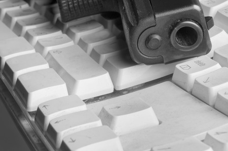 barrel pistol: Looking down the barrel of a pistol laid on the old dusty computer keyboard, in black and white