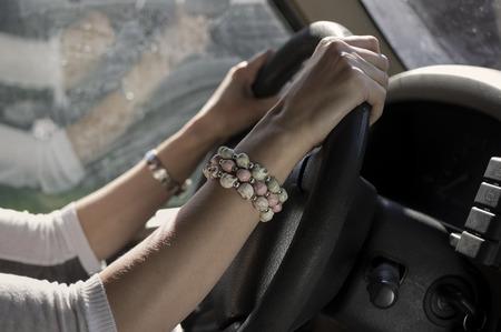 side shot: Side shot of female hands wearing bracelet on a steering wheel, reflection in the blurred background