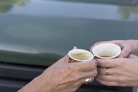 food and beverages: Two female hands, aged and young, holding cups of coffee in front of car, outdoor cropped shot