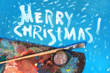 pallete: Artist palette and paintbrush next to Merry Christmas written text, holidays background Stock Photo