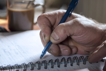 Hand of worker calculating profit or losses in notebook, indoor closeup with selective focus