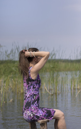 side shot: Side shot of a young woman relaxing on the lake shore, vertical shot