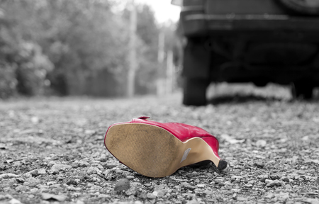 abandoned car: Abandoned red high heel in focus, car in the blurred background. Selective color shot, concept of danger on the roads