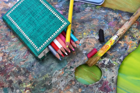 fine arts: Number of color pencils next to green book and artist palette, concept of fine arts and creativity
