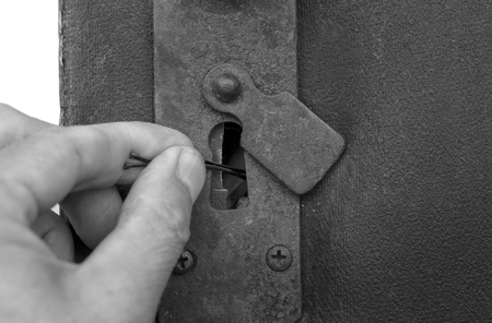 silently: A burglar hand, picklocking a door, closeup cropped shot with no people, concept of safety Stock Photo