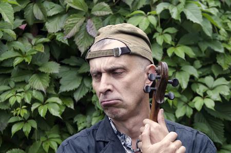 пышной листвой: Portrait of musician with exhausted gaze, holding violin, lush foliage in the background Фото со стока