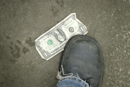 finding: One dollar bill under a human foot wearing shoes, concept of find and lost. Overhead shot