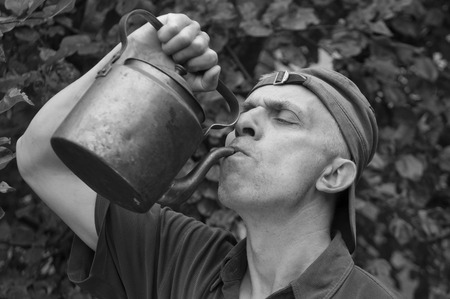 matured: Matured man drinking from a metal kettle, garden in the background. In black and white