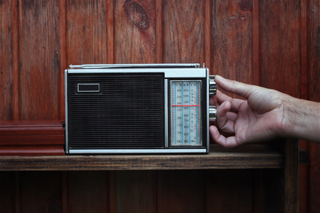 analogue: Male hand tuning the old receiver with analogue scale, listening news or music, next to wooden wall