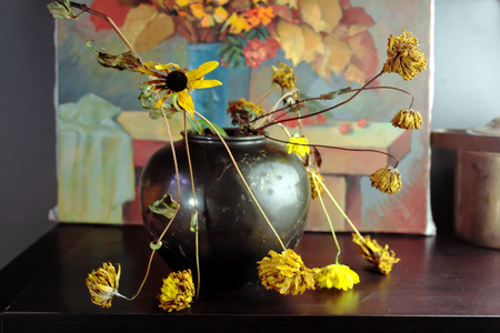 wilted: Wilted flowers in metal vase and painting of autumn bouquet in the background, selective focus indoor shot