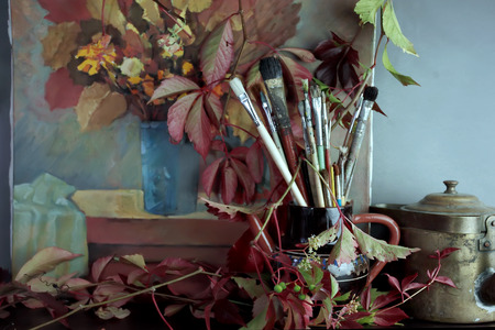 wilted: Artist brushes in vase, wilted grape leaves and artwork in the background, studio shot with selective focus