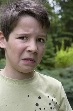 naughty boy: Boy of 10 with negative look on his face, outdoor vertical portrait
