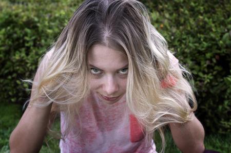 gaze: Jonge vrouw met lange witte haren en norse blik, groen park in de onscherpe achtergrond