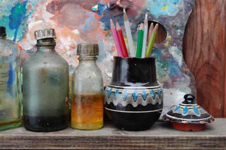 artist palette: Artist workshop with bottles of oil, pencils in vase next to artist palette, concept of creativity Stock Photo