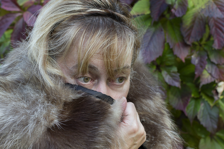 lush foliage: Portrait of a freezing woman wearing fur coat with collar up, lush foliage in the blurred background Stock Photo