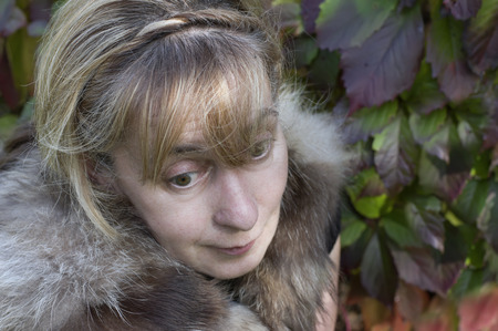 uncombed: Middle aged, wearing fur coat, woman dreamily rolls her eyes down, lush foliage in the background Stock Photo