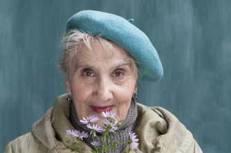 green beret: Portrait of a senior woman in green beret, holding flowers with a happy look at her face, outdoor shot Stock Photo