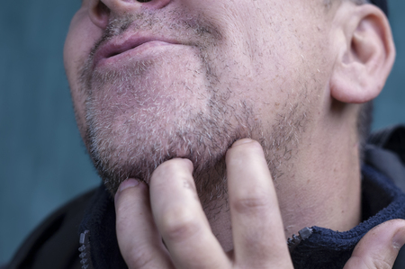 matured: Matured sneering man scratching his unshaven chin, outdoor cropped shot Stock Photo