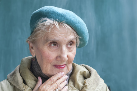 character traits: Senior woman in doubt holding her chin by hand, feelings and expression background