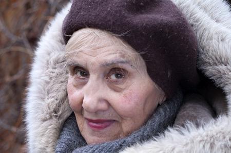 fur hood: Senior female wearing fur hood, outdoor closeup portrait Stock Photo
