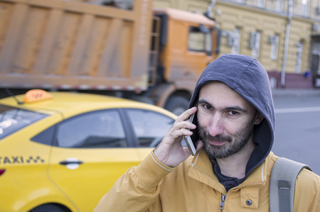 unshaven: Unshaven man in hood talking on mobile phone on a busy street