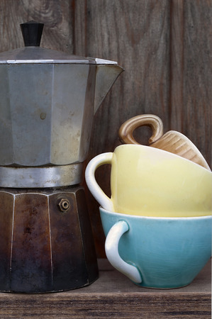 the next life: Well used metal coffee maker and pile of various cups next to wooden wall, vertical still life