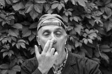 making face: Man with squint eyes and backward cap making face in stress, outdoor black and white shot Stock Photo