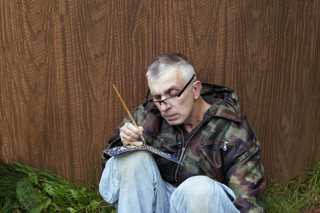 man nuts: Man looking nuts writing or painting by brush on a paper