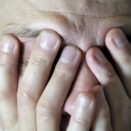 body expression: Man covering his face by hands in stress, closeup studio shot