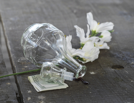 tipped: A table with a bottle of wine tipped over, next to hundred dollars bill and flowers. Concept of after party Stock Photo