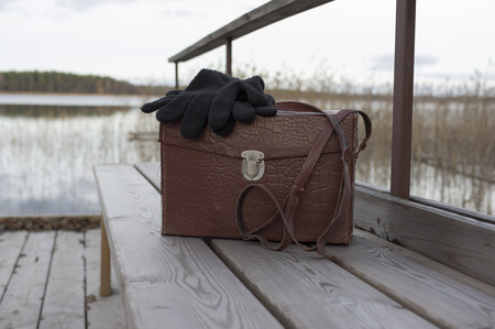 lost lake: Retro looking leather bag with woolen gloves on it laid on the pier, concept of travel