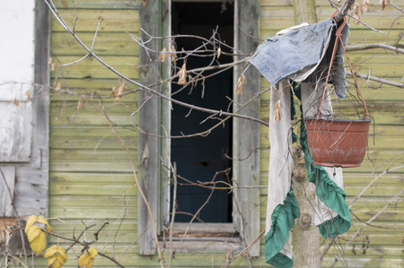 urban decline: Abandoned house with broken window and personal effects in the foreground Stock Photo