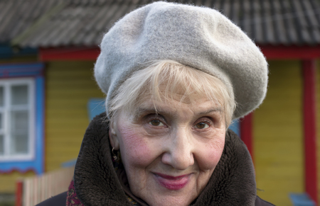 warm clothes: Portrait of a senior female wearing warm clothes, with a colorful house in the blurred background