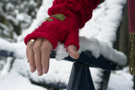 lean on hands: Female hand wearing red woolen glove laid on the armchair covered with snow, outdoor horizontal shot