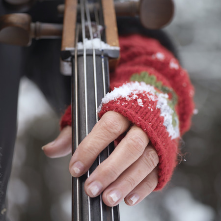 musical instrument parts: Musician hand wearing red woolen glove holding a cello, outdoor square shot