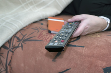 telly: Closeup of a female hand with remote control, selective focus indoor shot
