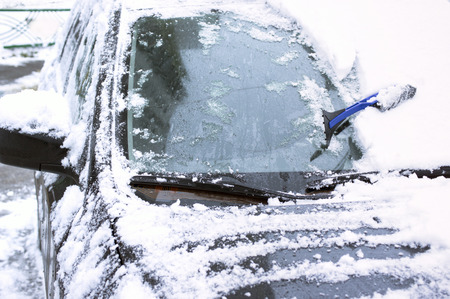 cropped shot: Scraper resting on a windscreen, snow removal from car. Outdoor cropped shot