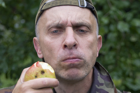 matured: Matured man chewing apple with a doubtful look at his face, outdoor horizontal shot