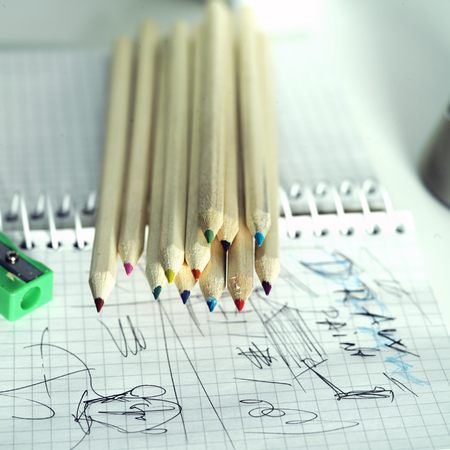coloured pencils: Coloured pencils and sketchpad with some ideas drawn, square indoor shot with shallow depth of field