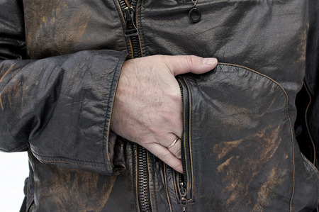 cropped shot: Man wearing leather jacket, hiding something while  keeping his arm in the pocket. Outdoor cropped shot