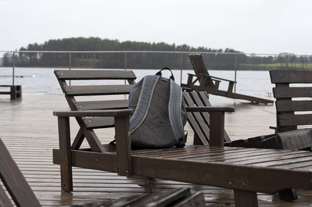 nasty: Abandoned rucksack on the wodden armchair, shot taken in a nasty weather day
