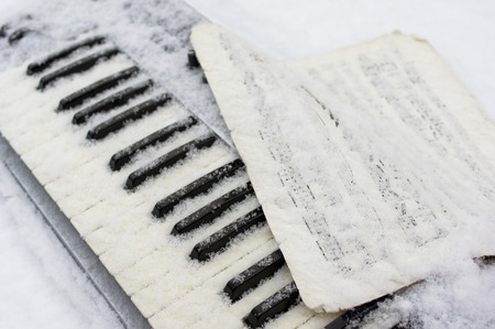 Keyboard and sheet music covered with snow, outdoor angled shot