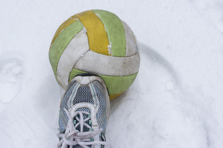 snow ball: Human foot wearing sport shoe over a football ball on the snow Stock Photo